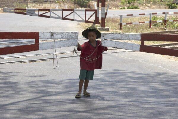 NIÑO ABRIENDO LA BARRERA DEL TREN EN LA CARRETERA DE BAGO A TOUNGOO