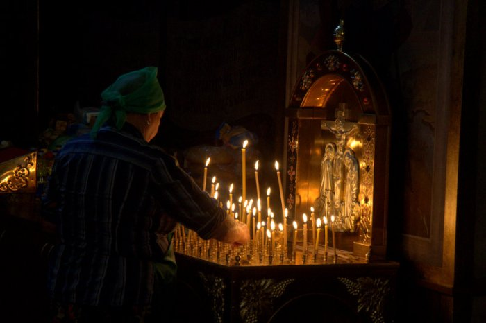 MUJER ENCENDIENDO VELAS EN EL MONASTERIO DE SAN MIGUEL, KIEV