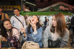 Girls eating stinky tofu at Jingmei Night Market Taipei