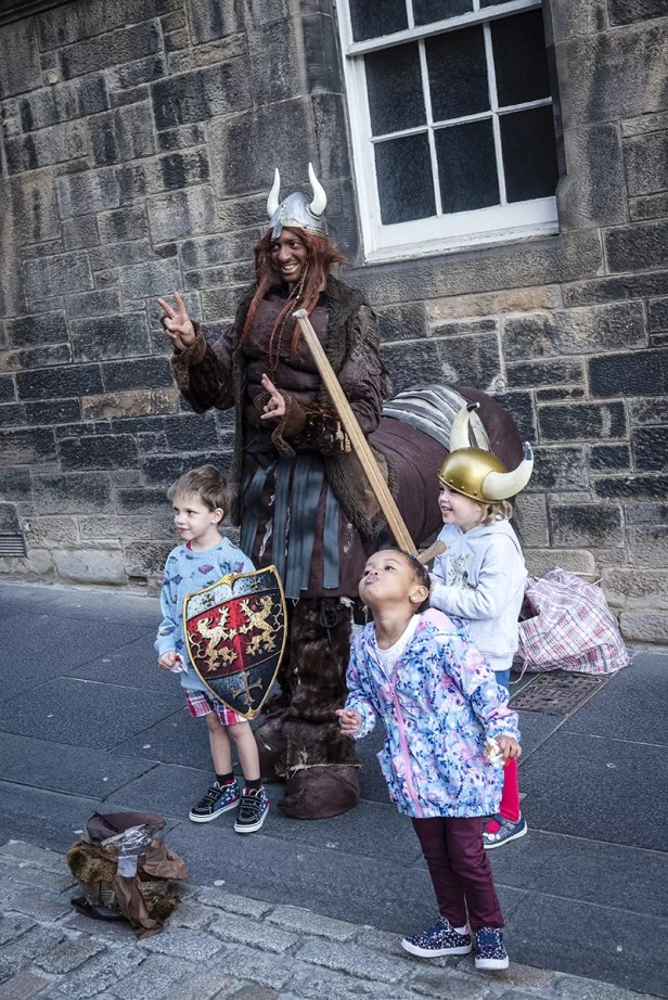 Centaur Street performer posing with kids on Royal Mile Edinburgh