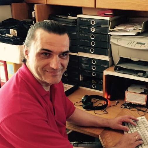 Zu sehen ist Harald, der an einem Computer sitzt und in die Kamera lächelt.