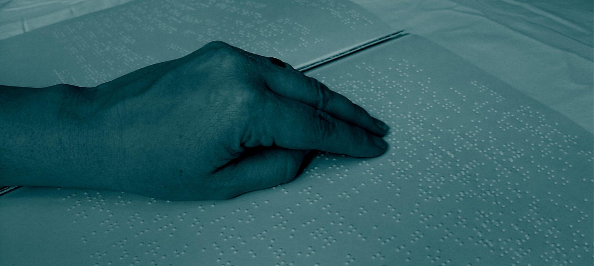 Hände die auf einem Blatt Papier Braille-Schrift lesen.