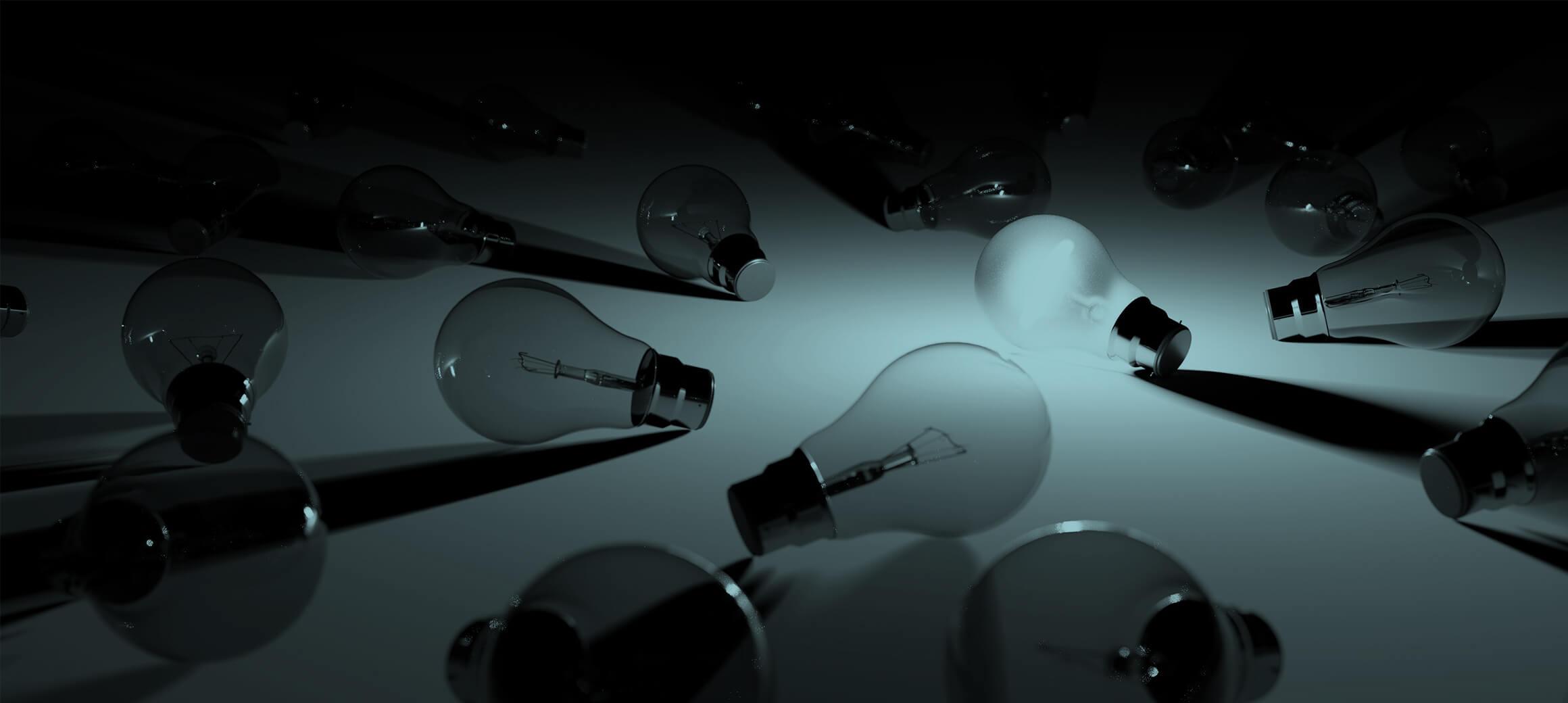 Glühbirnen die in Dunkelheit auf einem Tisch liegen, eine davon leuchtet.