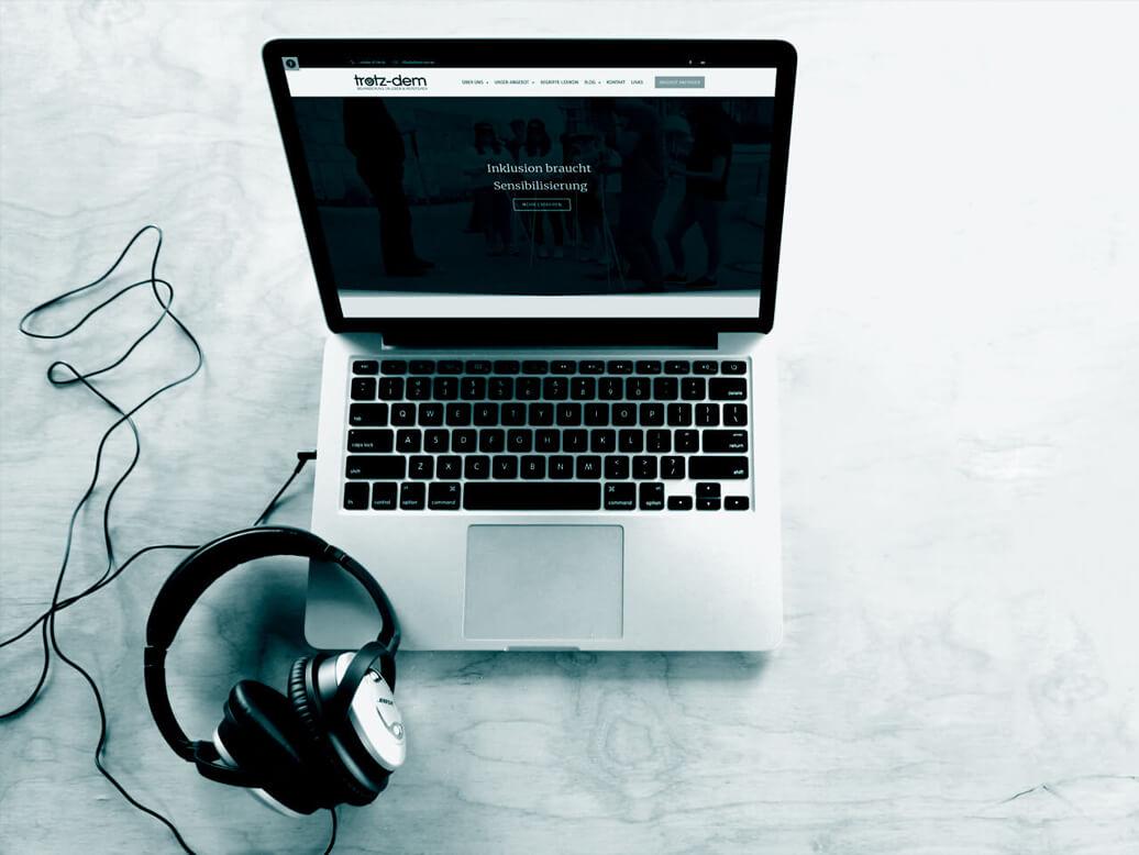 Ein Laptop der die TROTZ-DEM Website zeigt. Daneben liegen Kopfhörer.