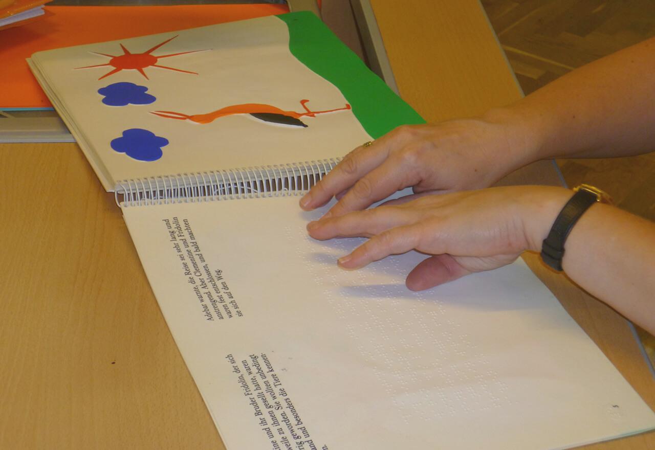 Sabine liest Braille Kinderbuch, man sieht ihre Hände auf dem Buch