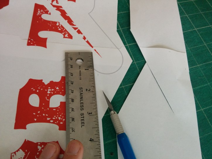 x-acto knife cutting away excess paper