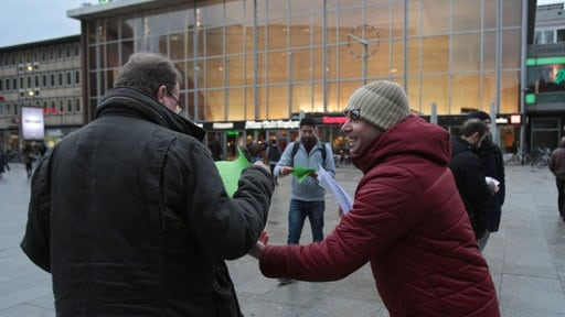 A Syrian refugee hands out leaflets condemning the assaults in Cologne. Credit: Syrians Against Sexism.