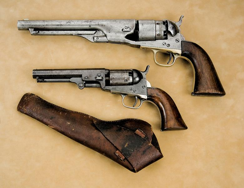 The .31 caliber, five-inch barreled 1849 Pocket Colt shown here is dwarfed by the .44 bore, belt model 1860 Army Colt above it. Because of the delicate and exposed percussion caps required to load these revolvers, shooters often carried the Pocket in flap holsters, like this half-flap scabbard.– Courtesy Little John's Auction Service / Anaheim, California –