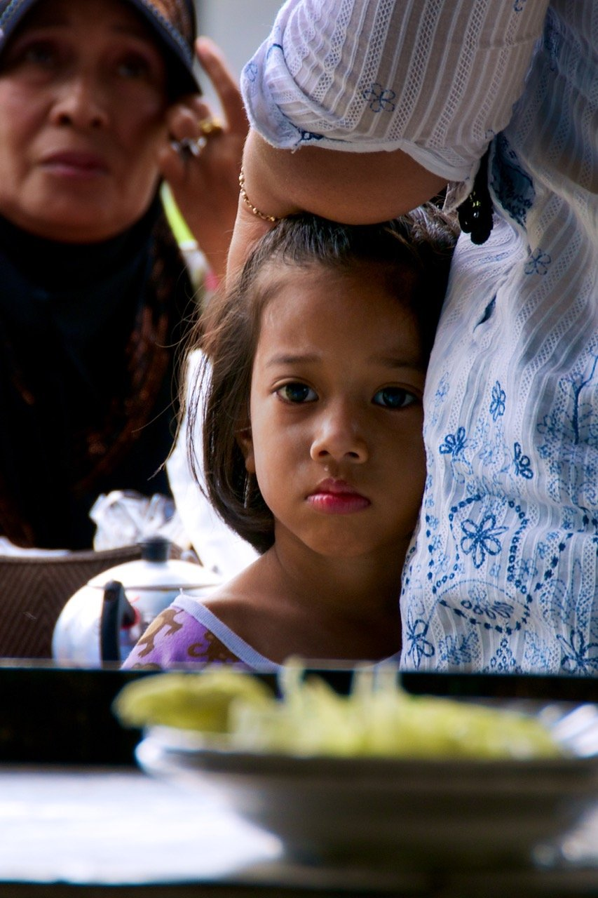 "A young girl looks on hungrily in Tha Sala in Nakhon Si Thammarat, Thailand, on Sept 27, 2012. Rice, chicken and—most critically—seafood make up a large part of the diet of the people in the area, which is also called ""Golden Bay"" by local residents because of its maritime wealth."