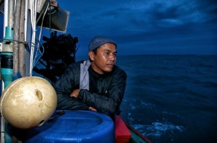 Night falls as Manit, considers where to pilot his boat next. Manit, as captain, is responsible for everyone on board, and his journeys often take them far out to sea in the pitch black night.