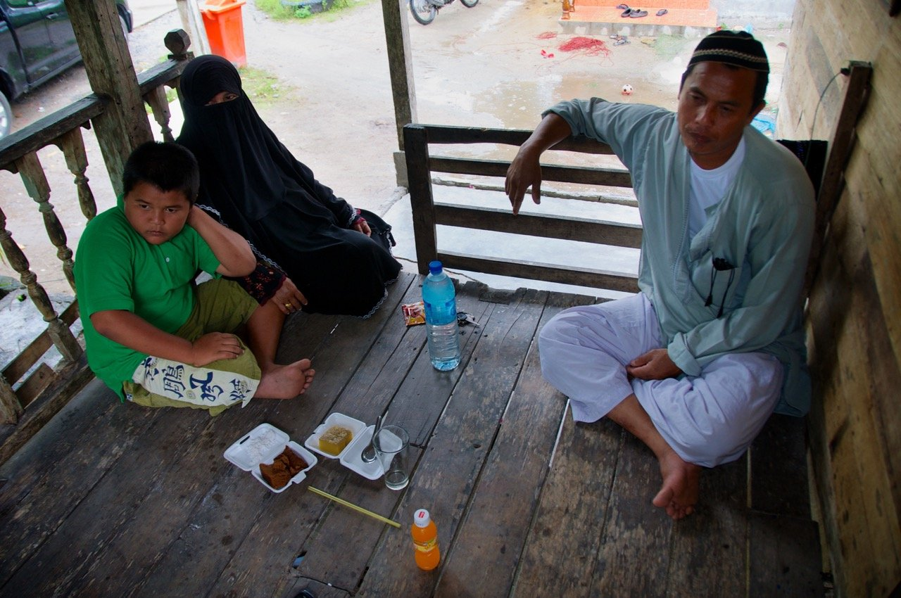 Manit Hankla, right, his wife, Romlha and their son, Muussin, discuss the challenges of a proposed coal-fired power plant in the area of Tha Sala in Nakhon Si Thammarat, which could devastate the sea-based industry here, which brings in almost $10 million annually. Hankla is a leading fisherman in the area, with generations of tradition behind him. Muussin is unsure if he will follow in his father's wake.
