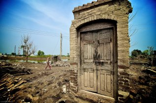 A woman walks behind the remains of a house destroyed by Pakistan's floods on Friday, Sept 3, 2010, after flood waters swept through the village of Mohammad Kot a month ago. Residents of Mehmood Kot have been waiting a month for relief aid, which they say they have not received.