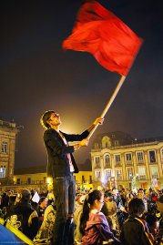 A a Petro supporter waves a red banner on Jan 10, 2014 in Bogotá. Given Petro's background with the leftist guerrilla group M-19, the imagery of revolution was abundant.