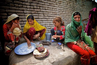 Girls of Mehmood Kot prepare bread for the remains of the village on Friday, Sept 3, a month after flood waters devastated their homes. Residents of Mehmood Kot have been waiting a month for relief aid, which they say they have not receieved.
