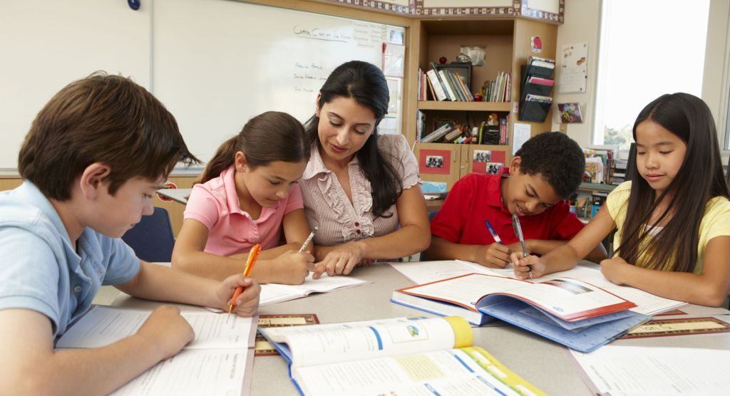 Teacher helping young students with schoolwork