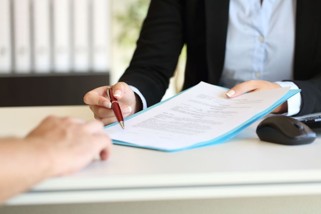 Employer handing background check consent form to job applicant