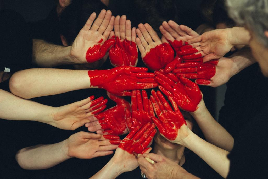 Photo of a heart painted on a group of hands portraying employees and employers working together