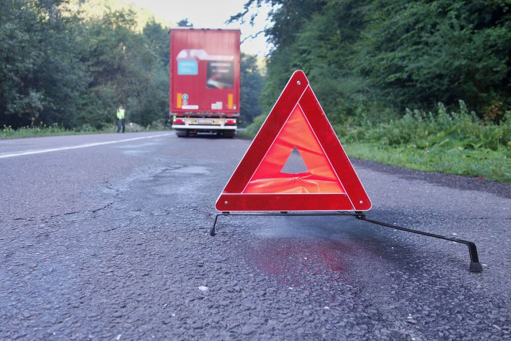 An orange warning triangle on the ground by a semi truck stalled on the side of the road
