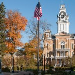 Hillsdale College campus during autumn, with an American flag displayed on a common area in front of a multi-storied brown brick building with white trim. The courtyard in the foreground shows green grass, numerous trees in various autumn colors and a clear, deep blue shy overhead.