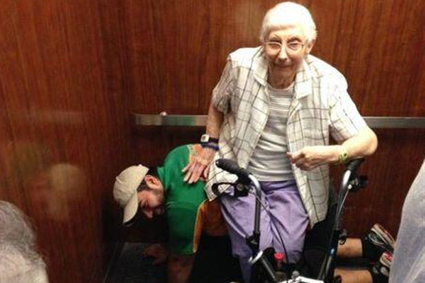 6. Young man acts as a human bench for elderly lady stuck in an elevator