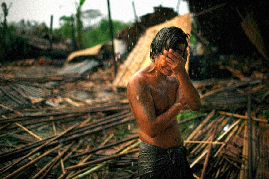 30 of the most powerful images of all time - Hhaing The Yu, 29, holds his face in his hand as rain falls on the decimated remains of his home