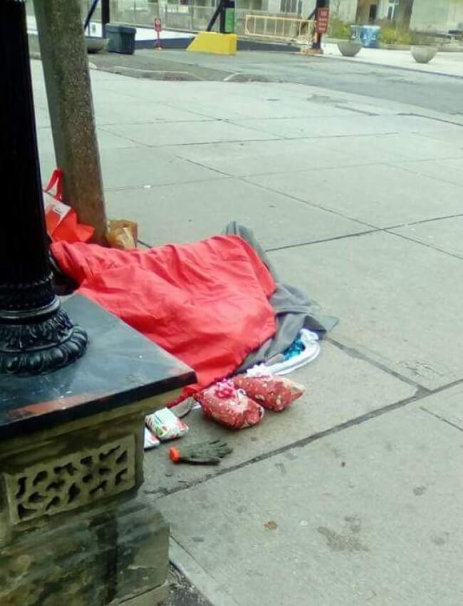 16. A homeless man sleeping on Christmas morning in downtown Toronto with Christmas presents waiting for him.