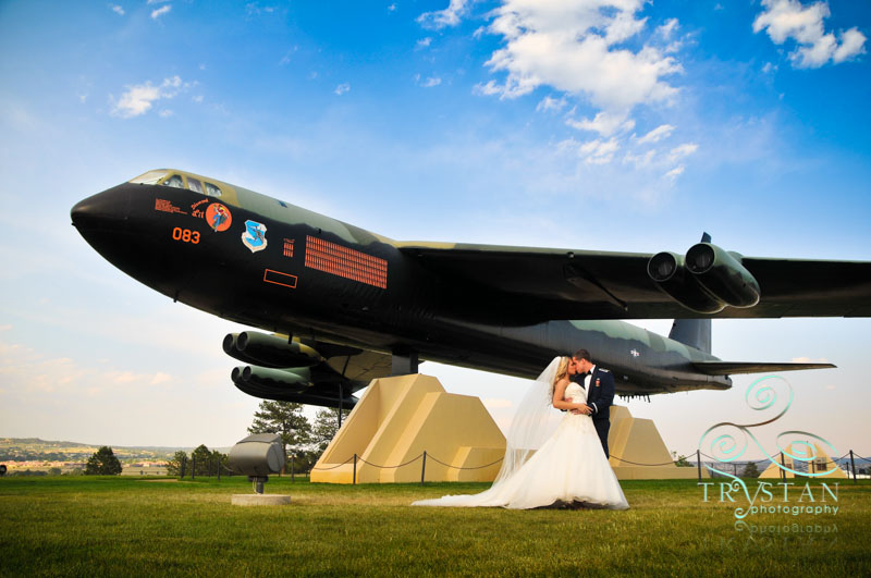 The bride and groom posing next to the B-52 monument on the Air Force Academy grounds.