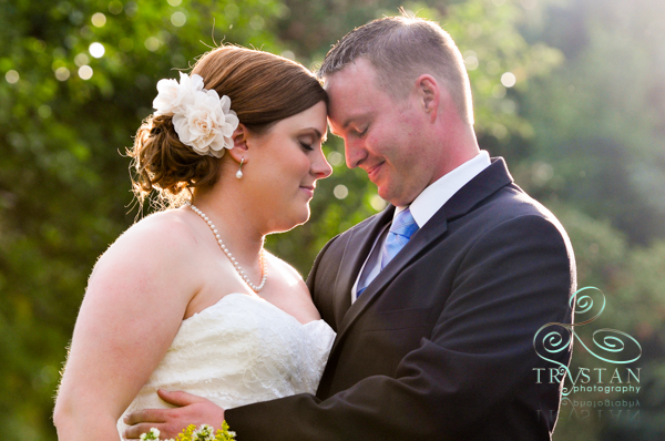 The birde and groom hugging in the back lawn of the Briarhurst Manor.