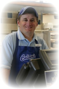 A TSE person served working at Culver's in uniform behind the cash register.