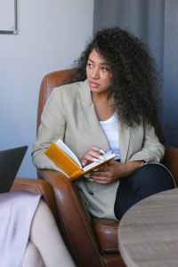 serious young woman with notebook in armchair