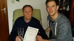 TSV-Vorsitzender Björn Strahberger übergibt Ehrenmitglied Alfred Baumann ein Präsent, eine Urkunde und die goldene Vereinsnadel.