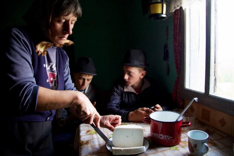 Mom Cutting Sheep's Cheese in Hom at Sheep Fold - Jina, Transylvania, Romania - Copyright 2014 Ralph Velasco