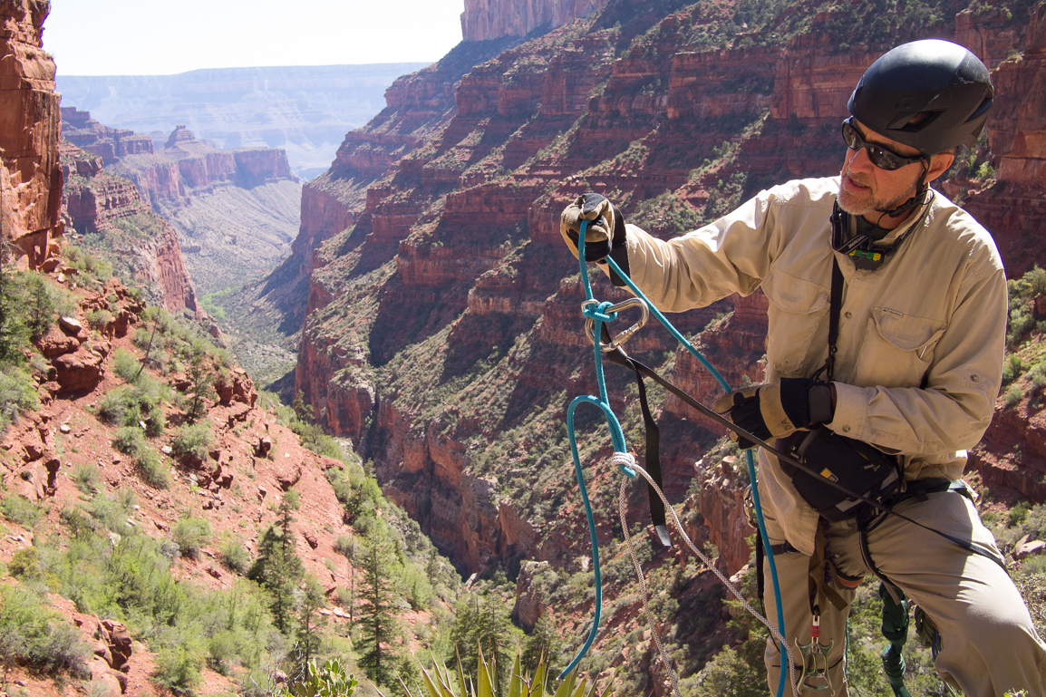 Dave demonstrating the 'biner block and pull cord system for the camera. This is a method for rappelling the full length of your rope. The black webbing (strap) over his knee is extended from a tree out to the edge of the cliff. At its end is a small steel carabiner. The blue rappel rope runs through the steel 'biner and is clove-hitched to a large carabiner so it can't pass through the small one. The white pull-cord is attached to the tail of the rappel rope by sort of a three-wrap sheet bend. Now we can rap the full length of the rope, and then pull it through the steel 'biner with the pull cord from the bottom. In general, I'm not a fan of clove hitches for life support because if it goes loose and there is movement in the system, the tail can be walked out of it. But with tension maintained (which the long rope does on its own), a long tail, and the tail secured by a pull cord that also has tension on it, I feel completely comfortable.