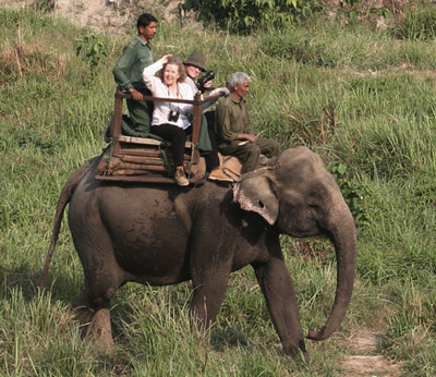 A mahout and tourists riding an elephant in Chitwan National Park.