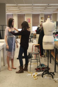 Araiza starts preparing for the beginning stages of fitting garment to her model.
