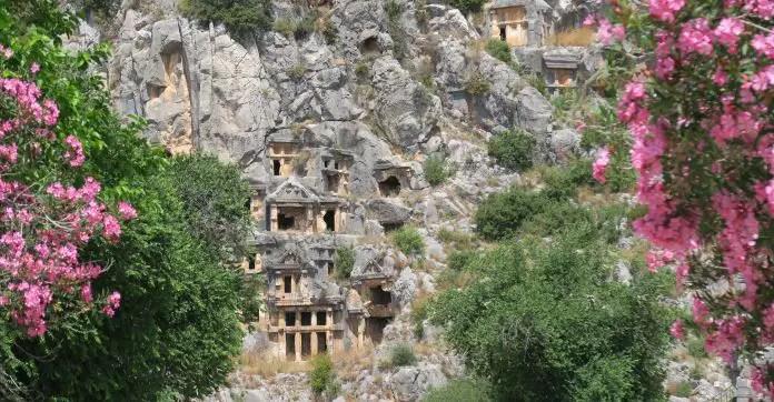Die in einen Berghang hineingehauenen Felsengräber der antiken Stadt Myra. Im Vordergrund sind rosa blühende Sträucher zu sehen.