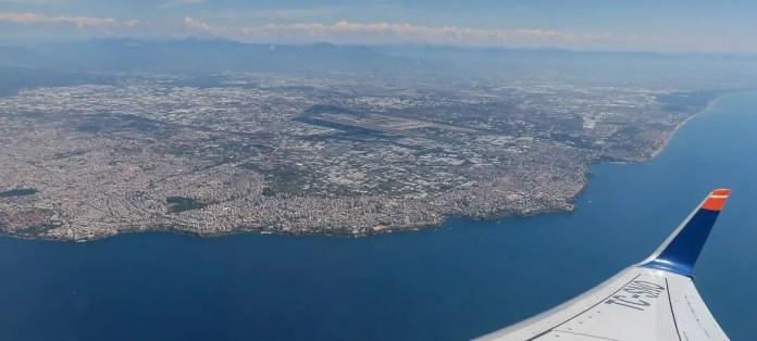 Blick auf den Flügel eines Flugzeuges und das darunterliegende Antalya mit den Landebahnen des Flughafen Antalya.
