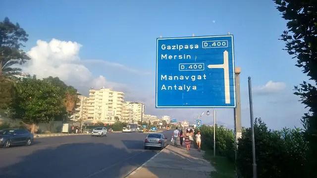 Foto der Schnellstraße und eines blauen Straßenschildes mit der Aufschrift Richtung Gazipasa/Mersin.