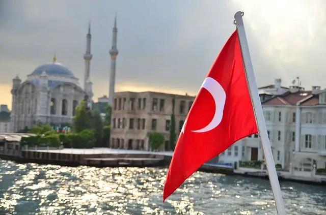 Flagge der Türkei am Heck eines Bootes. Im Hintergrund ist eine Moschee in Istanbul zu sehen