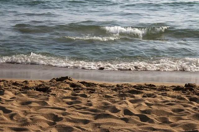 An einem Sandstrand brechen die Wellen des Mittelmeeres an der Küste der Türkei