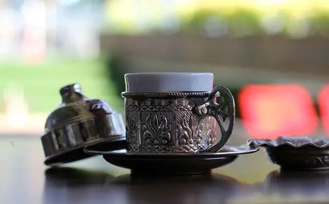 Metalluntertasse in die eine Porzellantasse mit türkischem Kaffee gestellt worden ist. Daneben liegt ein Deckel für die Tasse auf einem Tisch