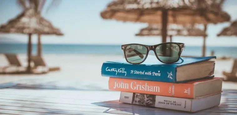Drei Bücher in roter, blauer und weißer Farbe sind auf einem Holztisch aufeinandergestapelt. Auf den Büchern liegt eine Ray Ban Sonnenbrille. Dahinter ist ein Strand, Sonnenschirme, Sonnenliegen und das Meer zu sehen.