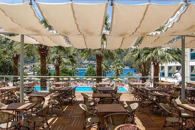 Restaurant in einem Clubhotel in der Türkei. Es ist mit weißen Tüchern überdacht. Der Blick geht Richtung der Poollandschaft. Im Hintergrund ist das Meer zu sehen.