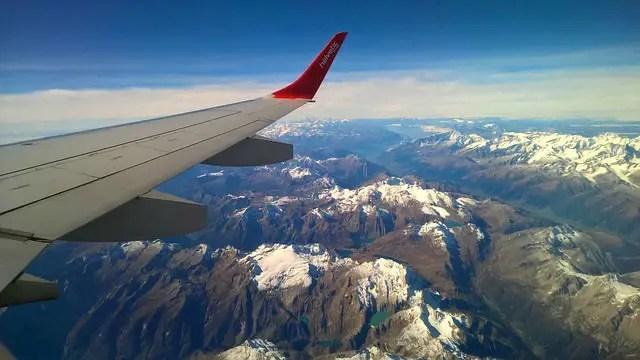 Flügel eines Flugzeges. Fotografiert aus dem Fenster in der Luft. Darunter sind die Alpen zu sehen.