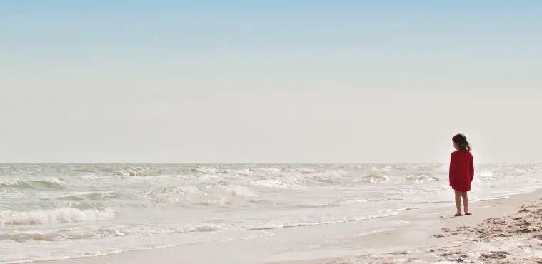 Ein Kind steht an der flachen Meeresbrandung an einem Strand. Es hat ein rotes Kleid an.
