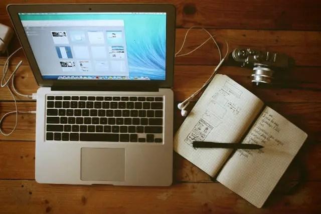 Notebook steht auf einem Tisch mit einem Notizblock.