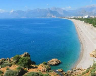 Utensilien die für einen Stranduraub in die Türkei mitgenommen werden sollten. Sonnenbrille, Sonnenhut, Kamera, Handy, etc. vor dem Kilometerlangen Konyaalti Strand in Antalya mit dem Taurusgebirge im Hintergrund.