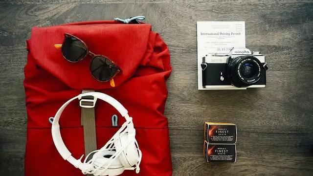 Roter Rucksack mit einer Sonnenbrille, Kopfhörern und einer Fotokamera auf einem Tisch liegend