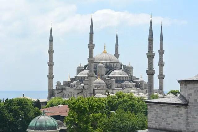 Aussenansicht der Blauen Moschee in Istanbul. Davor sind ein paar Grüne Bäume zu sehen und im Hintergrund der das blaue Meereswasser des Borporus.