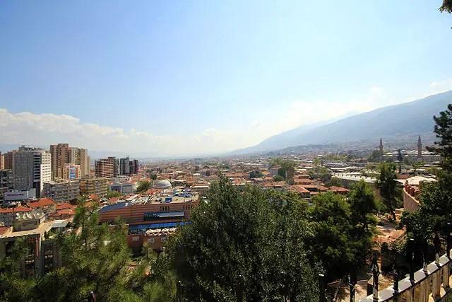 Panoramabild von einem Hügel auf die in der Innenstadt von Bursa stehenden Hochhäsuer und die dahinter am rechten Rand zu sehenden Berge